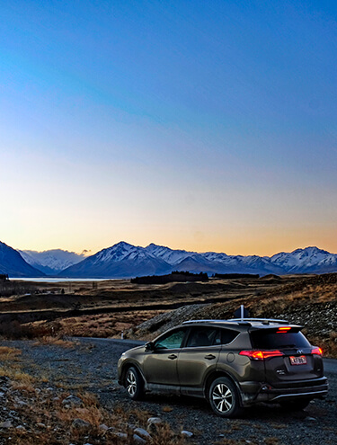 Portrait image of a Toyota Rav4 at dusk overlooking a lake and mountains of the South Island
