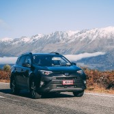 Image of a Toyota Rav4 with GO Rentals pink plates driving on a South Island road with mountains in the background
