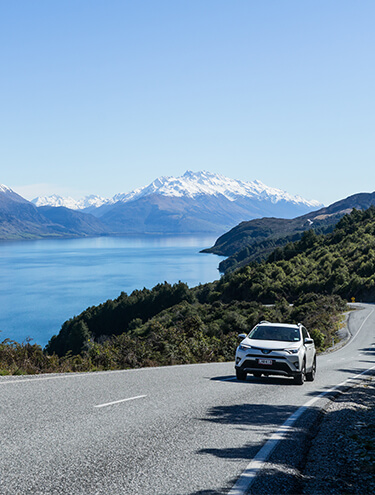 Image of a white Toyota Rav4 driving around Lake Wakatipu near Queenstown on a sunny day