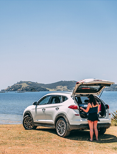 Image of a female looking in the boot of a Hyundai Santa Fe rental car parked next to the sea - mobile