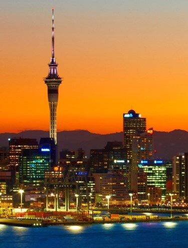 Image of the Auckland city skyline taken at sunset with the lights shining on all the buildings and in the port