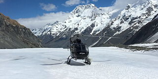 Image of a helicopter landing on top of one of the West Coast glaciers ready for a heli-hike