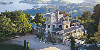 Aerial image of Larnach Castle and gardens with the Otago Peninsula in the background