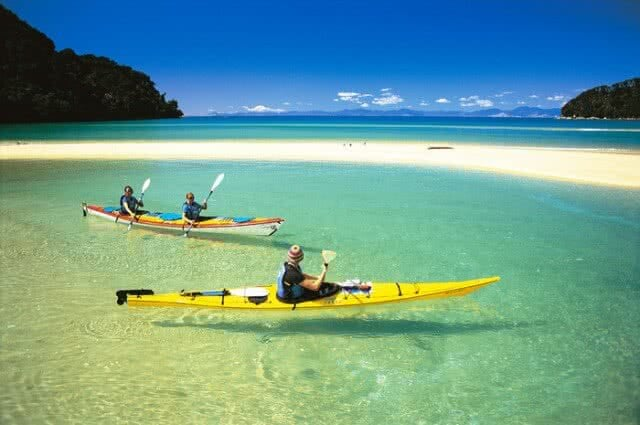 Image of people kayaking in the Abel Tasman National Park with crystal clear waters and golden sandy beaches