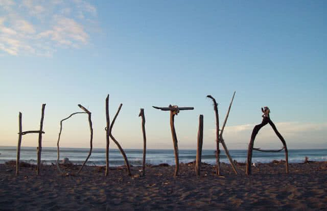 Image of the word Hokitika spelt out in sticks on the beach at Hokitika