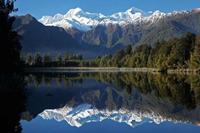Image of the Southern Alps and Mount Cook reflecting in the crystal clear waters of Lake Matheson