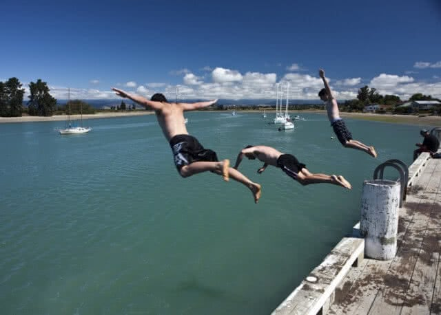 Image of lads jumping off the pier in Mapua on a sunny day