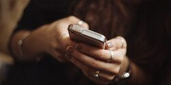 Mobile Menu image of a woman's hands typing on a mobile phone
