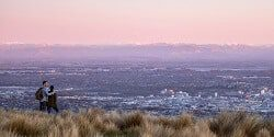 Image taken at dusk of two people looking down from the Port Hills over Christchurch - mobile