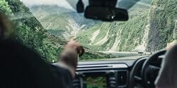 Hand pointing forward from the front seat of a car as two people drive down a steep road in the South Island