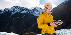Image of a climber in the snow on a mountain wearing a helmet and looking at a map - mobile