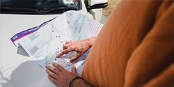 Image of a person studying a map of New Zealand planning a trip - mobile